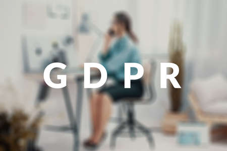 Blurred photo of a businesswoman sitting at her desk, making a phone call behind a GDPR text.