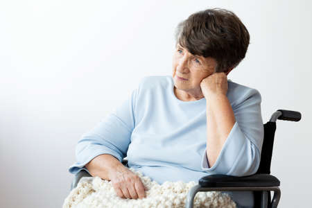 Sad disabled senior woman in a wheelchair against white background
