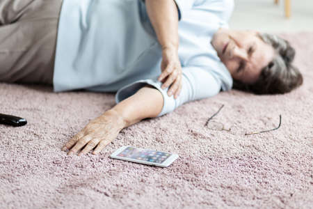 Close-up of senior woman with heart attack and smartphone on the floor