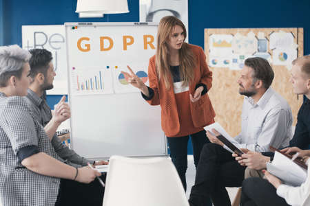 Team leader explaining the new General Data Protection Regulation to her employees in the meeting area of a company building. Stock Photo