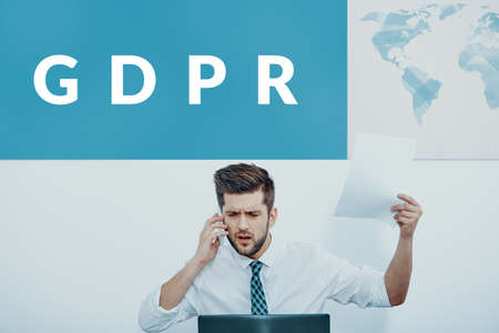 Angry businessman talking on the phone, sitting at his desk with a GDPR banner over his head.