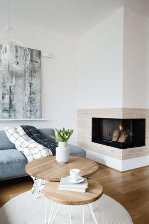 Fiori sulla tavola di legno rotonda all'interno del soggiorno scandi con camino e pittura grigia
