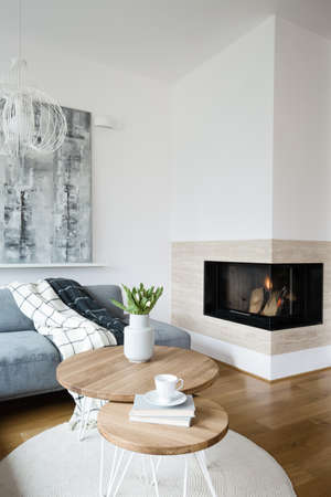 Flowers on round wooden table in scandi living room interior with fireplace and grey painting