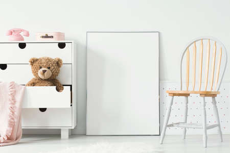 Poster with mockup between chair and cabinet with teddy bear in kids room interior. Real photo. Paste your poster here
