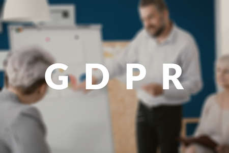 GDPR written over a blurred photo of w business owner explaining to his employees the steps needed to prepare for the new data protection regulation. Stock Photo - 102494631