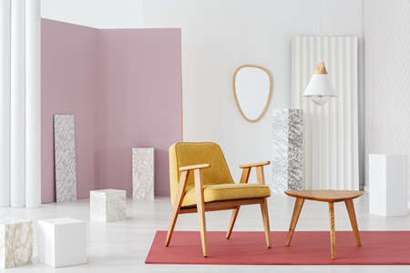 Mustard armchair standing by a wooden table in bright room interior with marble pillars and red carpet