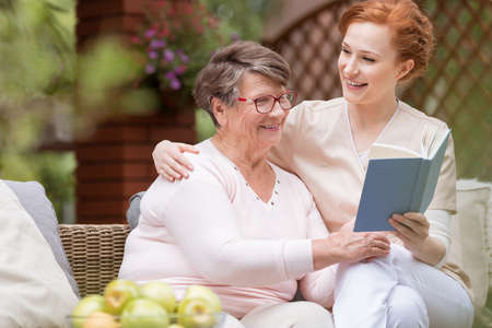 Cheerful senior woman with her tender caretaker reading a book together while relaxing outside. Close relationship. Foto de archivo