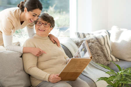 Grandmother sitting on a couch in a sunny room, looking at a photo album and sharing fond memories with a tender caregiver Banque d'images