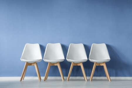 Vista frontal de una fila de sillas blancas modernas y sencillas contra la pared azul en un interior de sala de espera de estilo minimalista