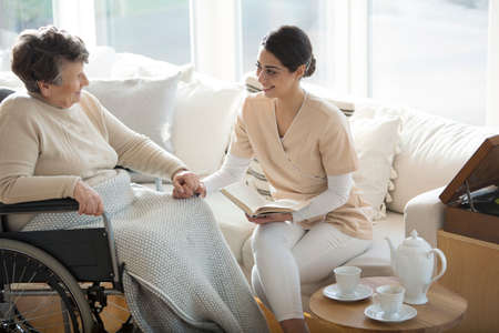 A disabled old woman in a wheelchair holding the hand of a tender professional medical assistant during tea time in a living room of luxury retirement home