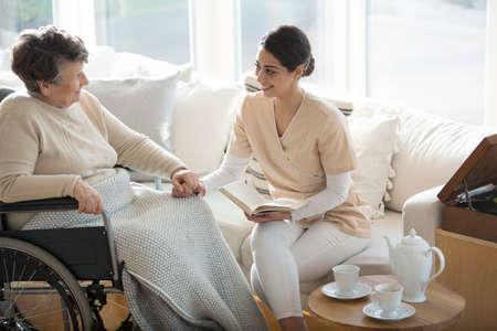 Een gehandicapte oude vrouw in een rolstoel die de hand van een tedere professionele medische assistent houdt tijdens theetijd in een woonkamer van een luxe bejaardentehuis