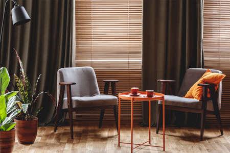 Vintage Sessel, orange Couchtisch mit zwei Tassen, Pflanzen am Fenster mit Vorhang und Jalousien in einem Wohnzimmer Interieur stehen