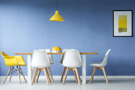 Minimal, modern dining room in interior with a table and contrasting white and yellow chairs around it, against blue wall with a mockup poster