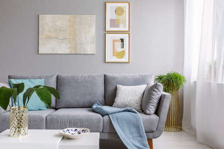 Real photo of a grey sofa standing in a stylish living room interior behind a white table with leaves and in front of a grey wall with posters Stock Photo
