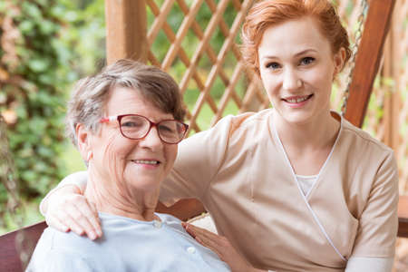 Close-up of a professional caregiver sitting next to and holding her arm around a senior lady on a patio outside of a family home.