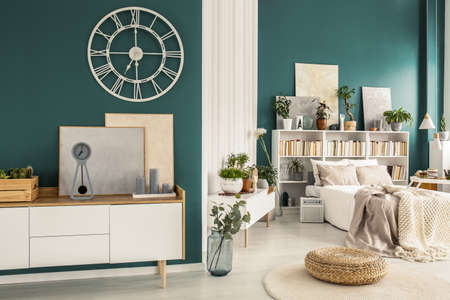 Old-fashioned clock with roman numbers on a turquoise green wall above a white scandinavian design sideboard in a stylish open space interior Stock Photo