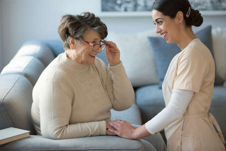 A tender caregiver kneeling down and facing a smiling older woman who is sitting on a sofa and holding her glasses