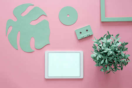 Copy space on tablet against pink background with green leaf, plant, cassette and frame