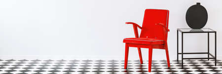 Red armchair standing in white room interior with checkerboard linoleum floor with place for your sofa Stock Photo