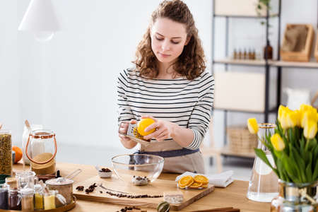 Young female entrepreneur preparing vegan soap from natural ingredients in the workshop of her organic cosmetics shop