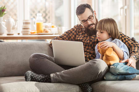 Kid with toy sitting next to his father and watching a movie on a laptop Stock fotó