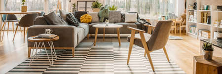 Horizontal photo of a scandi living room interior with a corner sofa, pillows, armchair, striped carpet and window in the background