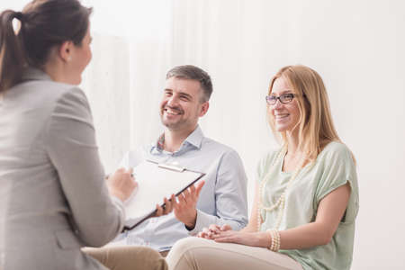 Psychotherapist analyzing a young, happy married couple in a bright office Stock Photo