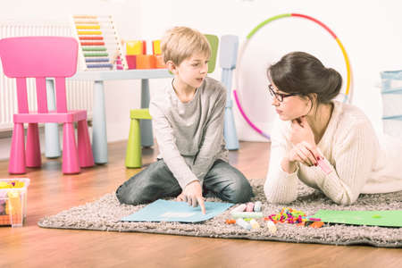 Private tutor and a small boy learning and playing at home. Fun teaching concept Stock Photo