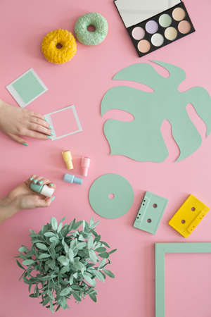 Woman with green nail polish at desk with donuts, make-up palette, yellow cassette and plant