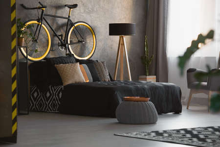 Modern bedroom interior with decorative cushions on black bed, a bicycle on the bedhead and copper tray on gray pouf. Real photo