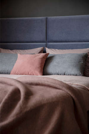 Grey and pink pillow on bed with headboard in woman's bedroom interior