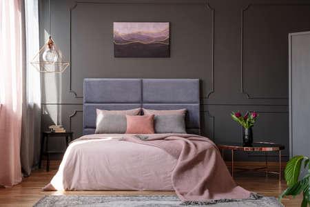 Tulipanes en mesa de cobre junto a la cama rosa contra la pared gris con moldura con póster en el interior del dormitorio