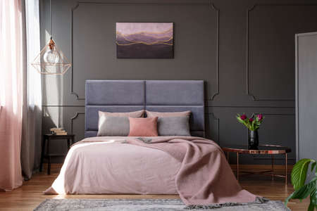 Tulips on copper table next to pink bed against grey wall with molding with poster in bedroom interior Фото со стока