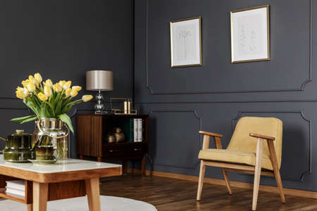 Wooden cabinet in the corner of a dark living room interior with wainscoting on the wall with posters next to a yellow armchair and table with tulips. Real photo