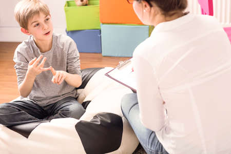 Little boy with learning difficulties talking to a child psychologist Standard-Bild