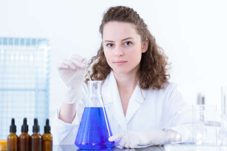 Female scientist stirring a blue mixture in a laboratory flask with a glass rod during pharmaceutical medicine test Reklamní fotografie