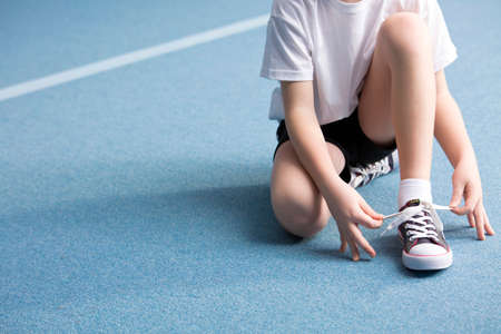 Close-up of kid tying a shoe on blue floor at the gym 스톡 콘텐츠