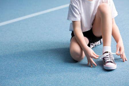 Primo piano del bambino che lega una scarpa sul pavimento blu in palestra