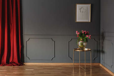 Pink tulips on a golden table in the corner of a luxurious interior with molding on dark gray walls and bright red curtains. Real photo