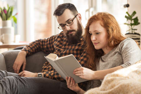 Woman and man reading a book. Lovely couple at home concept Foto de archivo - 102592336