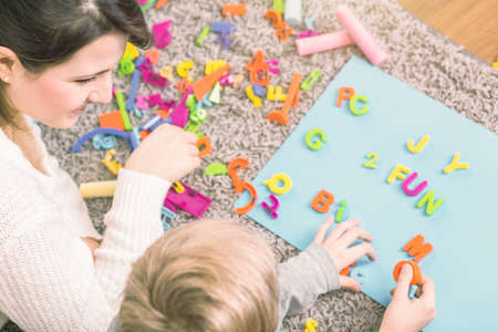 Young boy learning letters during a session with speech therapist 스톡 콘텐츠