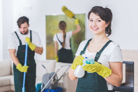 Group of young, hard-working professional cleaners in dirty apartment. Woman with cleaning solution and cloth against blurred background