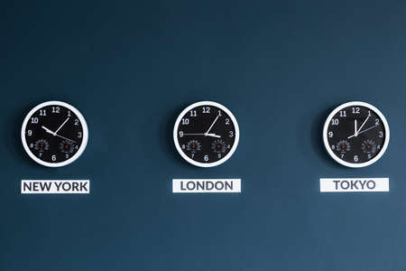 Black clocks on navy blue wall in businessmans home office interior 版權商用圖片