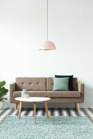 Front view of a sofa with pillows, coffee table, chandelier and green carpet set on a white wall in living room interior