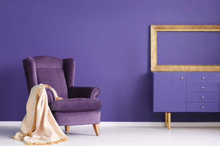 Gold blanket on purple suede armchair in living room interior with mockup of empty frame