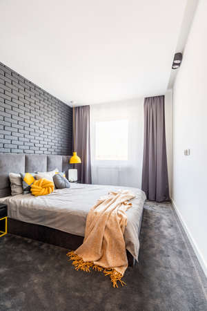 Yellow blanket on bed in grey bedroom interior with brick wall and drapes at window