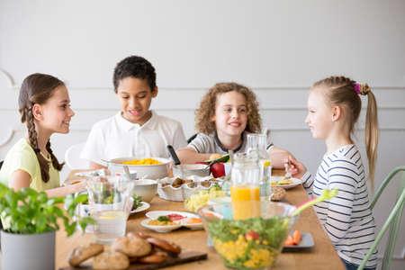 Smiling kids eating dinner while celebrating children's day at home