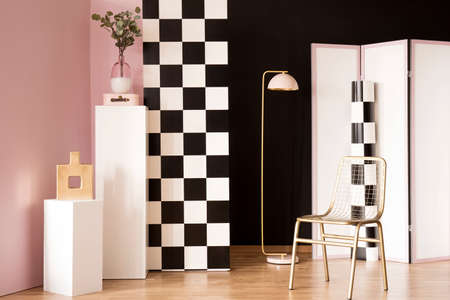 Gold chair next to pink lamp in pastel interior with checkerboard wall and plant on white pedestal