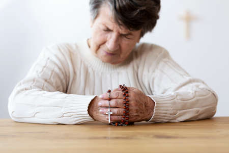 Religious senior woman praying with red rosary in the church. Focus on the hands