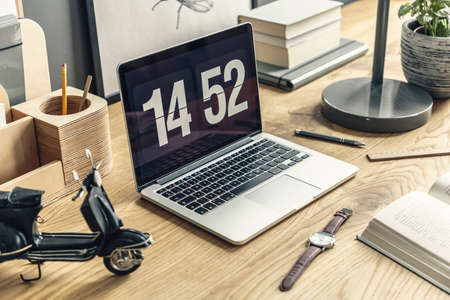 High angle of wooden desk with laptop, clock and black toy in freelancers workspace interior